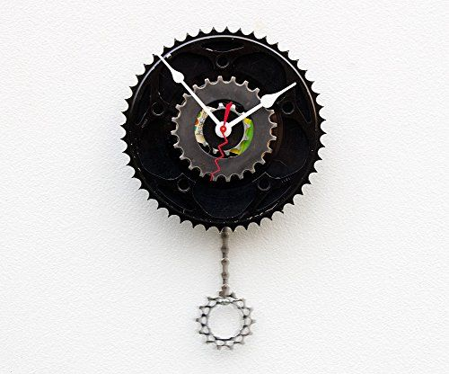 """Recycled Bike Gear Clock, Wall clock, upcycled bike gift, modern wall clock, pendulum clock, upcycled bicycle parts clock, repurposed cycle parts clock. This clock was created using a recycled bicycle chain ring gear, a 45 record, 3 smaller bike cassette gears, some bike chain and a new quarts drive movement with pendulum. The pendulum does work and is comprised of a piece of bike chain and a small cassette gear. This clock measures approximately 7.5"""" W x 12"""" H. It would make a great..."""