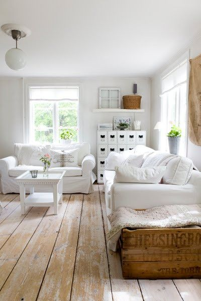 White slipcovered sofas, scrubbed pine floors, linen shades on the windows - fresh & simple