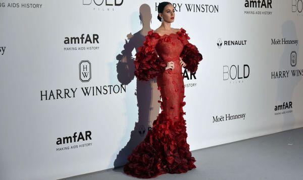 DRAMATISK: Katy Perry hadde en av kveldens mest omtalte (og hyllede) kjoler i motepressen. Den røde kjolen er fra Marchesa, og artisten stylet antrekket med røde lepper og glatt sveis. Foto: AFP