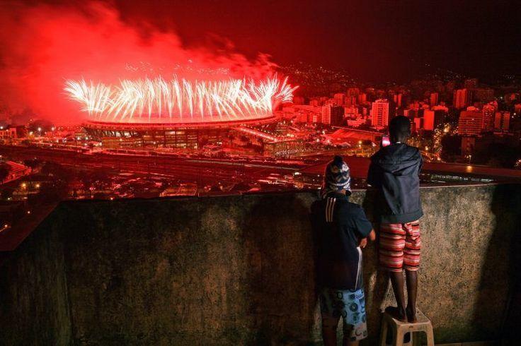 <p>L'illustration des contrastes de la ville de Rio de Janeiro : pendant qu'une partie de la ville célèbre les Jeux Olympiques, les enfants des favelas doivent se contenter de contempler. (Photo : AFP)</p>