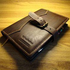 Оригинальный кожаный цвета черного шоколада Handmade ежедневник формата А5, легко заменяемый, с кольцом-держателем для авторучки, тремя слотами для карт, закрывающийся на застежку-пряжку. Коричневая кожа премиум класса выделана и прошита вручную, на лицевой стороне кожаной обложки вытеснено брендово