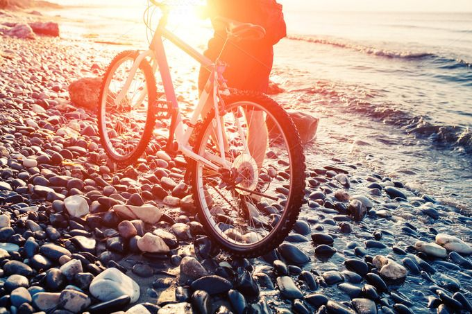 Man with bicycle on a sea shore by odpium on Creative Market