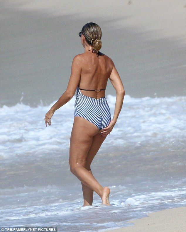 Looking rear-ly great: Her backless striped swimming costume showed off her pert behind