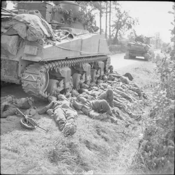AUG 15 1944 The Gordon Highlanders push forward in Normandy Men of the King's Shropshire Light Infantry resting next to a Sherman tank of 3rd Royal Tank Regiment, 15 August 1944.
