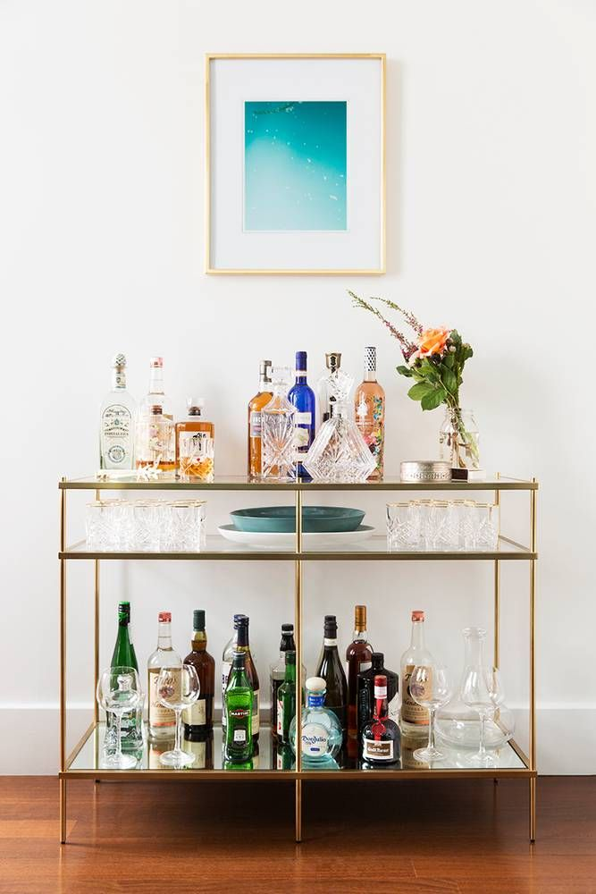 simple contemporary gold and glass barcart with single piece of artwork in turquoise above