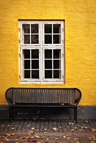 Mustard wall and black bench.