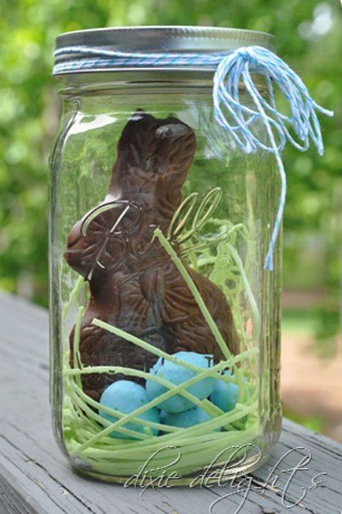 Fill a Mason Jar with an unwrapped chocolate Easter bunny, edible grass, and candy eggs for a visually appealing Easter treat.