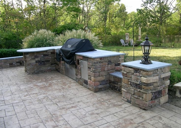 An outdoor kitchen with a built in grill and two storage cabinets and a second side with a radius counter for lots of seating.