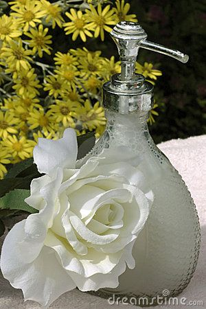 Liquid soap  and silk rose in a sunny garden with yellow flowers in the background