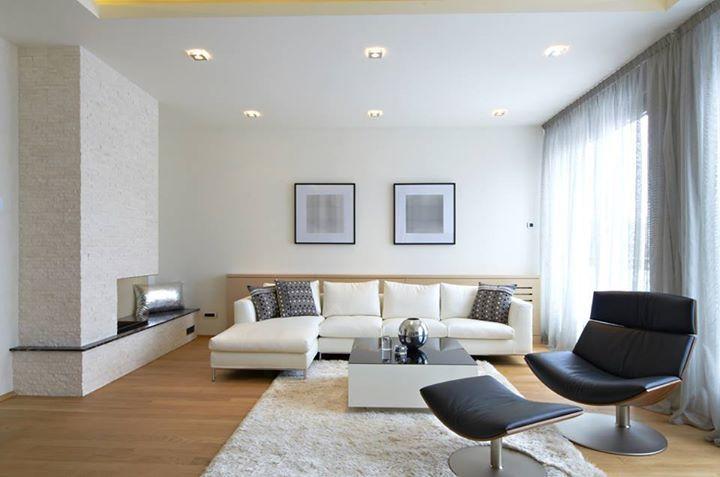 """""""Příjemný obývací pokoj v tlumených barvách přírodních materiálů. Oceňuji důraz na kvalitu, zvládnutou kombinaci různých povrchů a citlivou práci s textiliemi. Závěsy od stropu až k podlaze prostor zvyšují. Koberec """"kolíkuje"""" epicentrum. Vhodně je zvoleno osvětlení rastrem bodovek v kombinaci s nepřímým osvětlením z podhledu. Ještě mi tam chybí lampa na čtení u praskajícího ohně a bylo by to dokonalé."""""""
