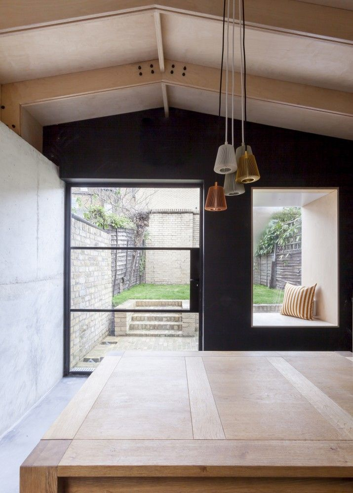 Plywood House / Simon Astridge. Window seat and crittal door in side return kitchen extension