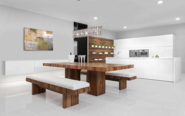 Kuchyňská linka Line / Elite v čistě bílém laku. Kuchyňská linka je netradičně doplněna o masivní jídelní stůl a sezení v podobě lavice v dekoru selský dub.