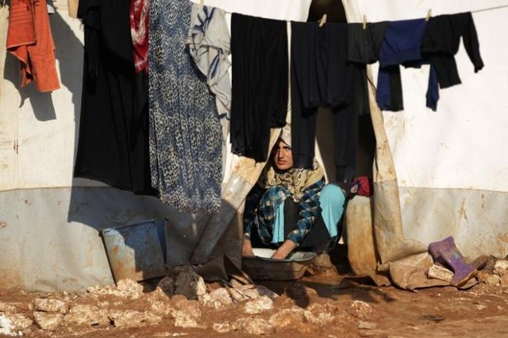 An internally displaced Syrian woman washes clothes inside her tent at the Bab Al-Salam refugee camp, near the Syrian-Turkish border, northern Aleppo province, Syria January 19, 2017. REUTERS/Khalil Ashawi