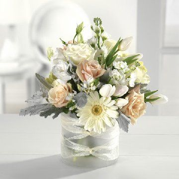 A dainty frosted glass vase is ribbon wrapped and holds cream roses, white tulips, stock and Gerber daisies.