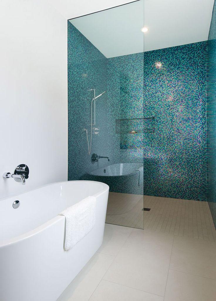 Stupendo mosaico blu scuro con riflessi dorati in questo moderno bagno minimal con vasca in ceramica bianca e box doccia