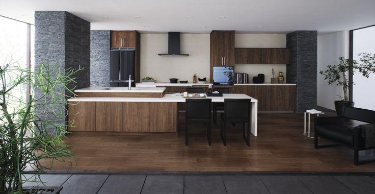 キッチンと床材の柄をウォールナット柄で統一。 さらにダイニングテーブルはキッチン本体と同じ人造大理石で作り、空間全体でトータルコーディネイト。 重厚感のある、居心地のよい空間が実現しました。