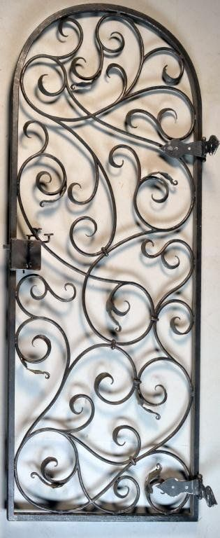 """Having an arched top, overall leaf and scroll decoration, heavy lock, 76"""" H x 31"""" W, circa late 19th- early 20th century"""
