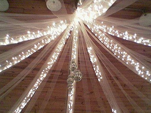 Tulle and twinkle lights as wedding decoration overhead! Very inexpensive and eye catching!