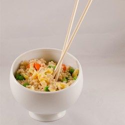 A great way to use up leftover rice, this quick fried rice cooks up with frozen peas, baby carrots, eggs, and soy and sesame sauces.