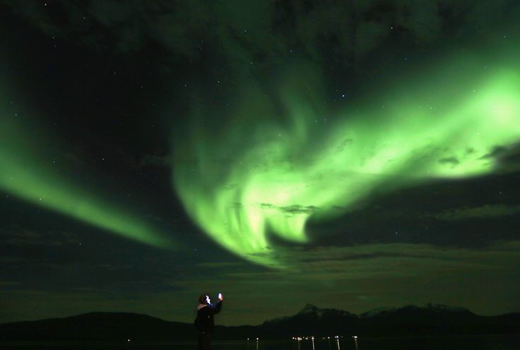 A tourist takes photos of an Aurora Borealis (Northern Lights) over the Bals-Fiord north of the Arctic Circle, near the village of Mestervik, Norway.