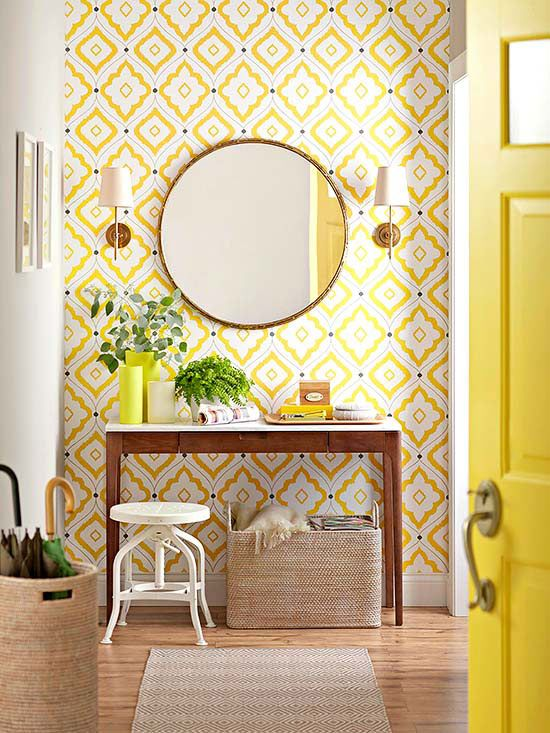 entry vignette: yellow wallpaper, narrow console table, plants, round mirror