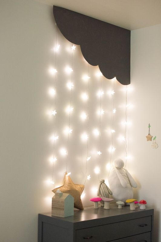 cozy and whimsical corner of a kids room with star lights hanging from the ceiling