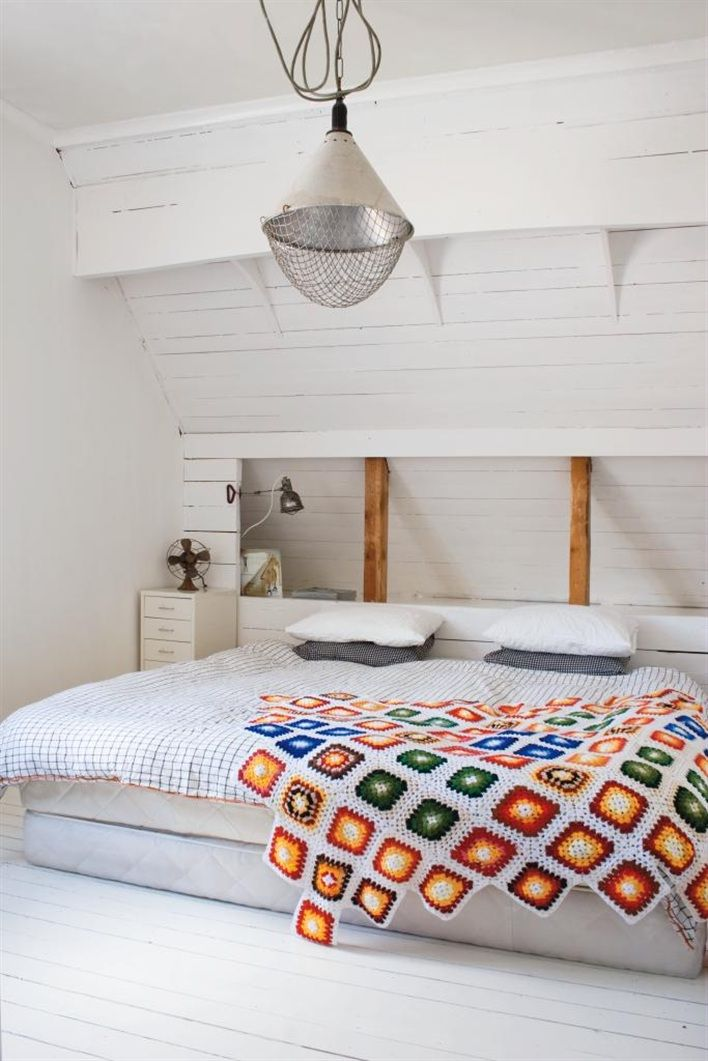 Love the built-in headboard idea here. Also, white paint and textiles throughout an attic or any other small space can do wonders for making it feel more spacious.