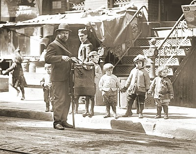 n organ grinder on the streets of New York's Lower East Side attracts a captivated audience, circa 1910.