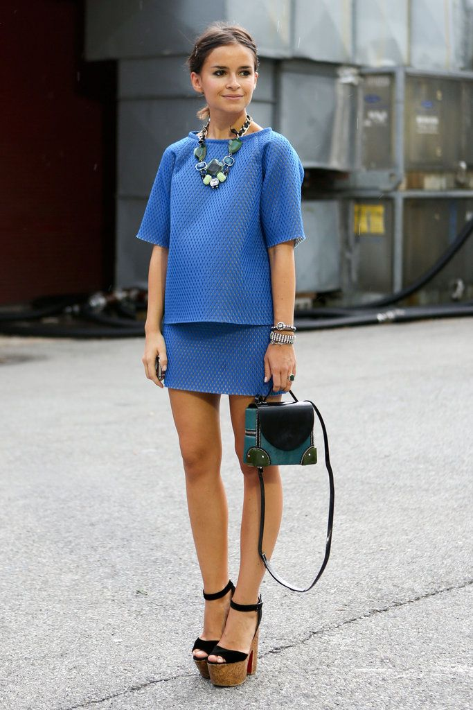 Miroslava Duma charms outside the tents — just statement jewels and a chic blue skirt set.