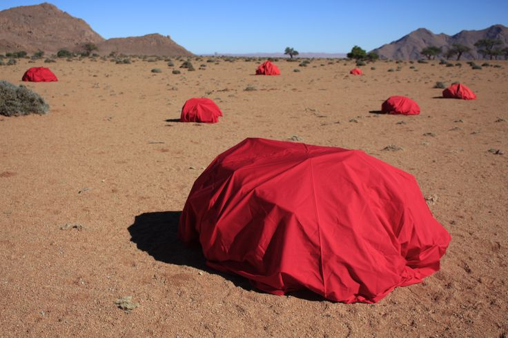 Wrapping bushes with red fabric. Namatib. Namibia