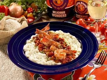 Grits: 6 cups water  2 cups half and half Salt to taste  ¼ tsp white pepper 2 cups quick grits ½ cup grated sharp white cheddar cheese 4 tbsp unsalted butter cubed   Shrimp:  1 tbsp olive oil  2 cloves garlic, minced ½ cup diced onion ½ cup diced celery ½ up diced carrots 1 can (14.5 ounces) diced tomatoes ¼ cup diced roasted red peppers ¼ tsp paprika 1/4 tsp crushed red pepper flakes ¼ cup basil chiffonade Salt to taste 2 pounds shrimp. Peeled and de-veined tails left on