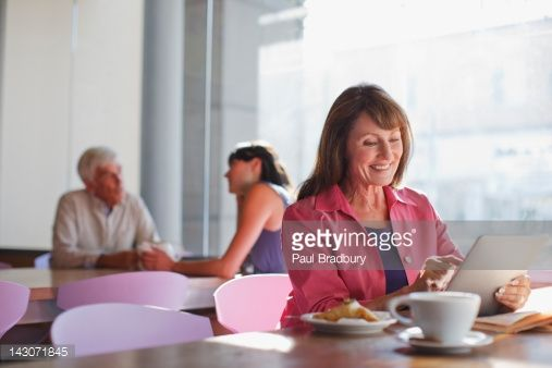 Stock Photo : Woman using tablet computer in cafe