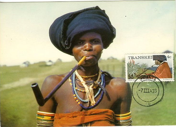 Africa | Xhosa woman smoking a traditional pipe. Transkei, South Africa | Scanned stamp card