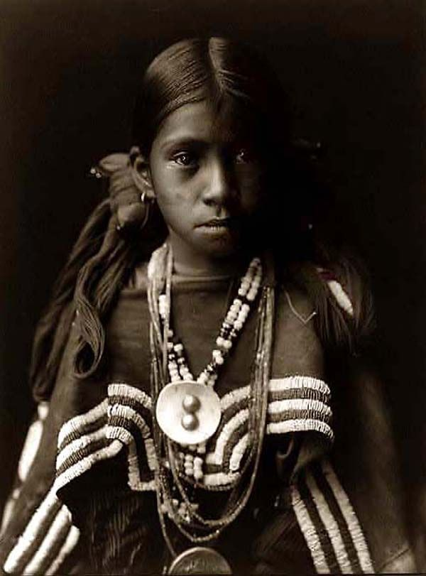 Here for your perusal is an original photograph of a Jicarilla Girl wearing a Feast Dress. It was created in 1905 by Edward S. Curtis.    The photograph illustrates a Jicarilla Apache girl, in a half-length portrait, wearing dress with buckskin cape, several necklaces, medallions; her hair is tied on each side of her head with large knot of yarn.