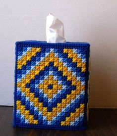 Made from 7-mesh plastic canvas and 4-ply yarn. Cover will fit a 4 1/2 (11.5cm) square box of tissues and is 5 3/4 (14.7cm) high. The stitch pattern is Mosaic stitch on the sides with Gobelin and Cross stitches on the top. Colors used are Royal, Skipper Blue, Yale Blue, Gold, and Pop Out Yellow. Item care: wash by hand with warm water and mild soap. Blot excessive water and let air dry. For shipping outside the US, please request price.