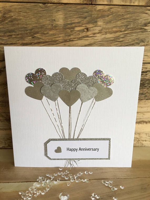 This lovely handmade Anniversary Card features heart shaped balloons cut from either different patterned silver or gold paper and card, with matching strings. The attached label is bordered in either silver or gold glitter card and finished with a small matching heart. The card has