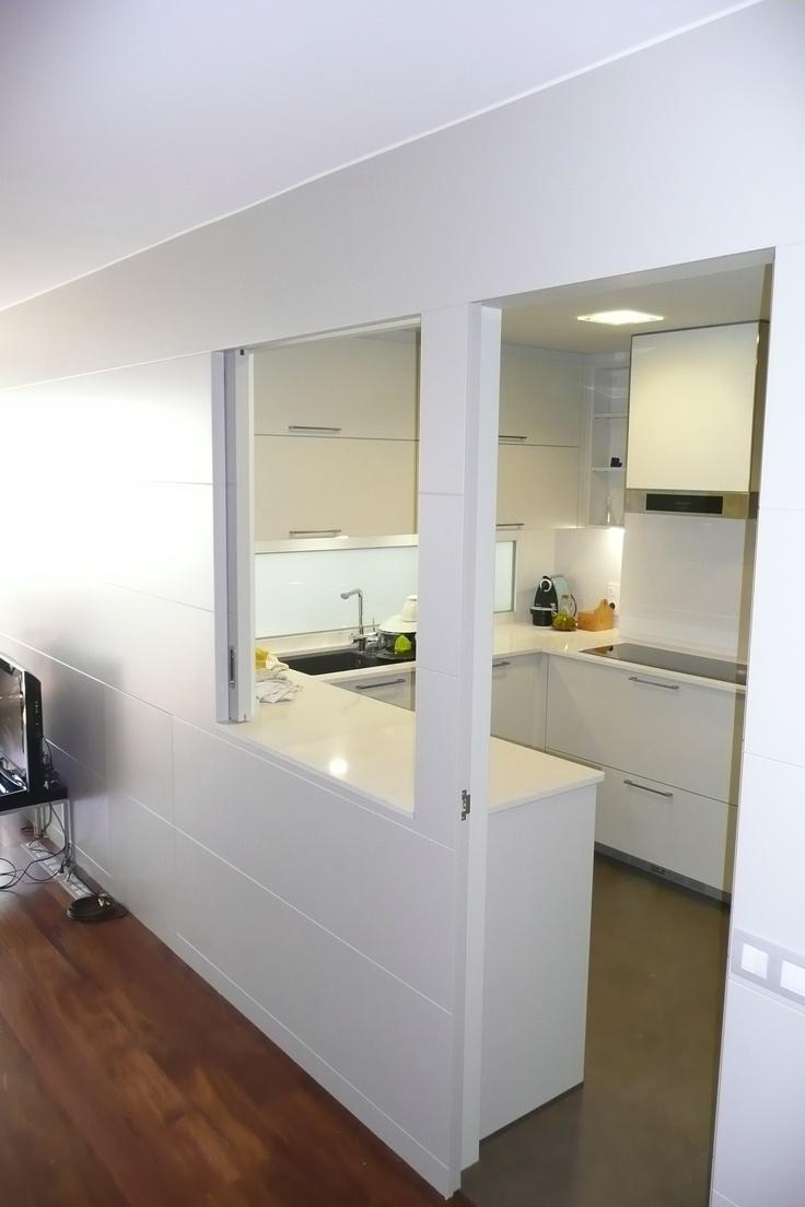 Cocina santos modelo ARIANE2 blanco seff con apertura pasaplatos a salón y ventana ciega pasaluz en zona de fregadera, campana panelada en blanco seff BY SMSTUDIO
