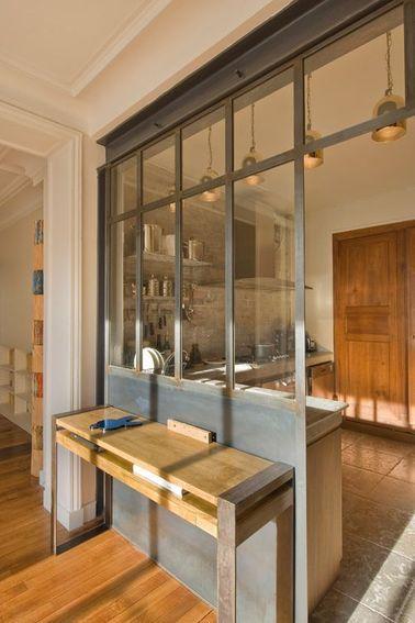 On se croirait projeté dans le repère d'un artiste avec cette verrière atelier qui sépare la cuisine du salon. Le soubassement de la verrière sert de support à une console en bois patiné parfaitement assortie.