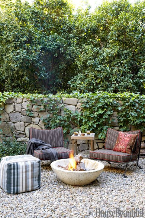 California Cool: In the backyard of designer Frances Merrill, a striped pouf, comfy chairs, and a stunning fire bowl invite you to relax with friends. Click through for more beautiful fire pit ideas.