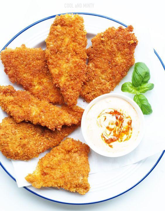 Cieniutkie i soczyste kawałki piersi kurczaka smażone w panierce z płatków kukurydzianych. Idealne na rodzinny obiad po powrocie ze szko...
