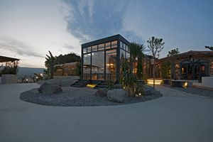 A restaurant designed by Cacti, the metal structure kitchen building is the focus of the restaurants' big garden.