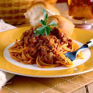 All in one spaghetti 1 pound ground beef  1 large onion, chopped 2 garlic cloves, minced 1 (8-ounce) can tomato sauce $ 1 (6-ounce) can tomato paste 3 cups tomato juice 1 cup water 1 teaspoon salt 1 teaspoon sugar 2 to 3 teaspoons chili powder 1 teaspoon dried oregano Dash of pepper 1 (7-ounce) package spaghetti, uncooked Grated Parmesan cheese Garnish: fresh Italian parsley sprigs