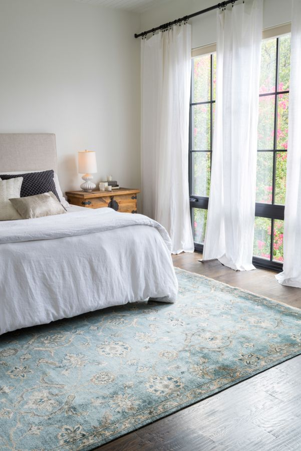 Light, airy bedroom. White sheets and drapes, light blue Persian/Oriental rug