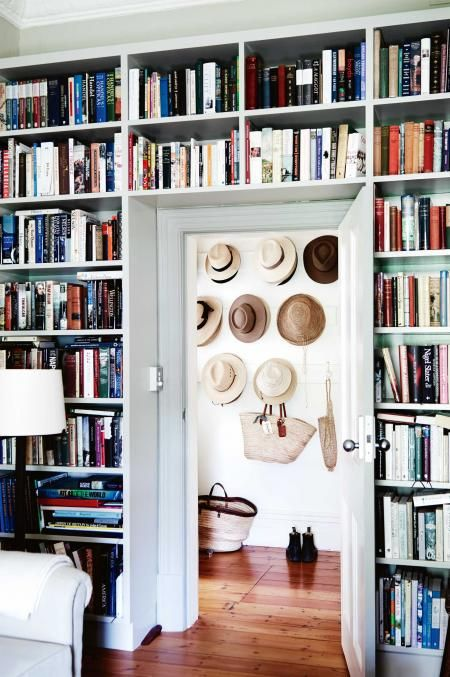 Room with wall of bookshelves and doorway into room with wall of hats. (detail of extension around door way to create appropriate depth for shelves