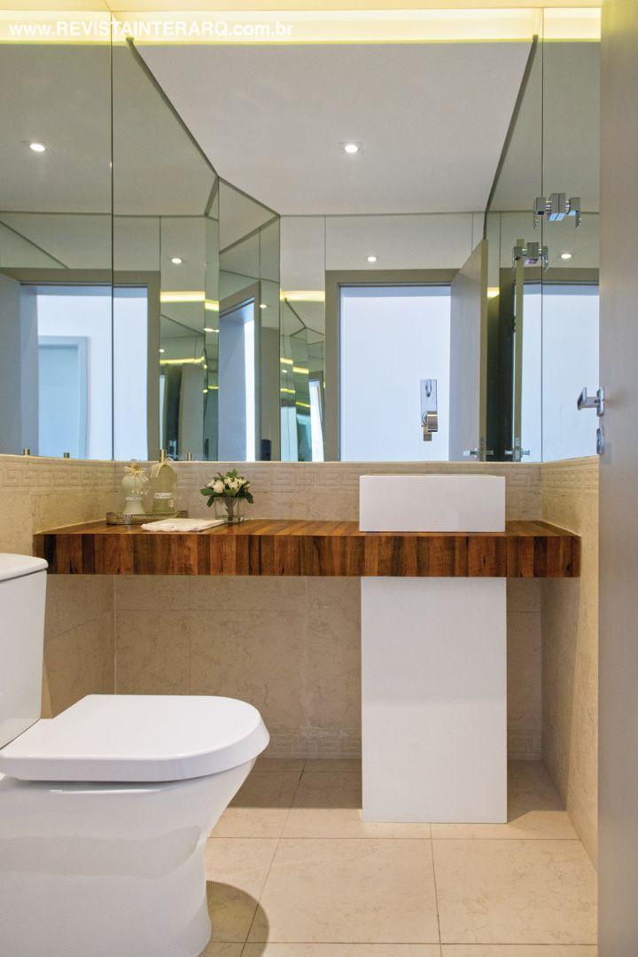 O lavabo clean exibe a cuba de piso quadrada em Caesarstone em sintonia com a bancada de madeira