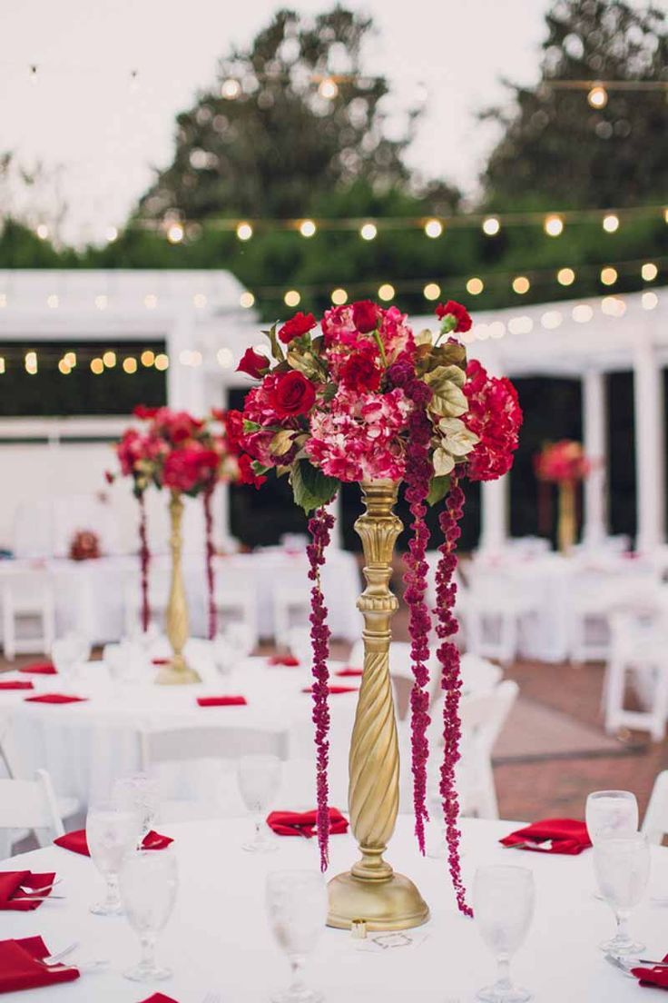 red floral centerpieces on reception tables with tall gold holder by Lee Forrest Designs-Red and white Cypress Grove Estate House Wedding in Orlando, FL - Photo: Lora Rodgers Photography-Orange Blossom Bride