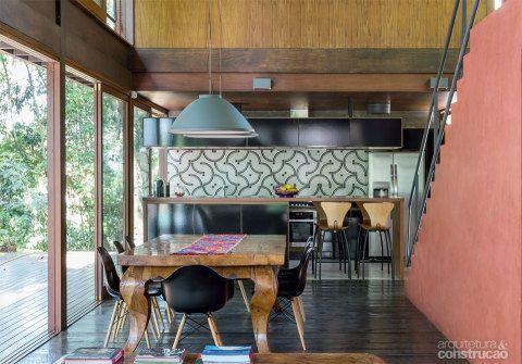 O piso dos ambientes de estar, no térreo, leva tábuas de canela de demolição. Ao fundo, a cozinha exibe uma faixa de ladrilhos hidráulicos da Ladrilar. Luminárias da Reka. Projeto Una Arquitetos.