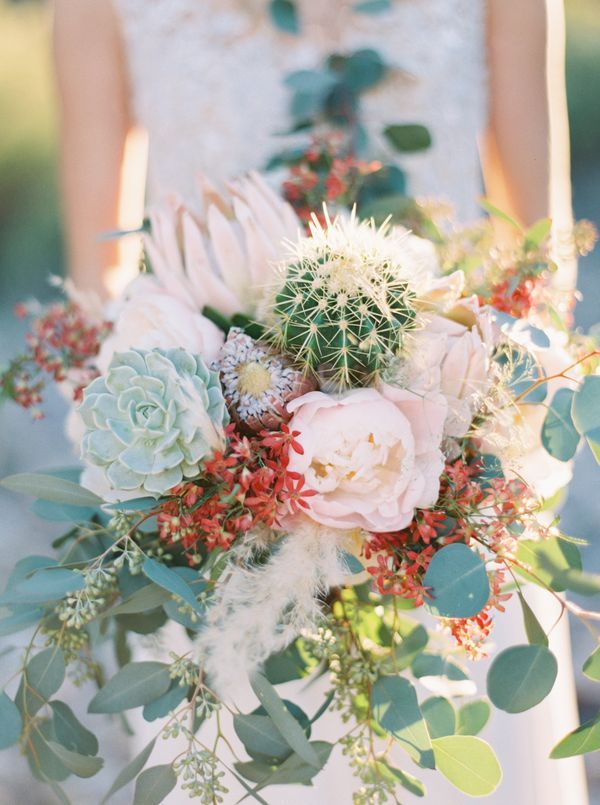 Wild & creative bouquet combines colorful flowers with cactus & succulents for a desert wedding.