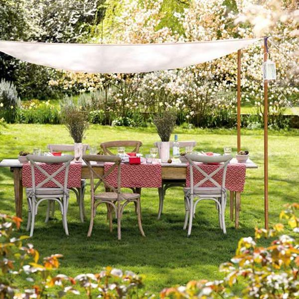 rustic chairs and table shaded by a simple cloth canopy