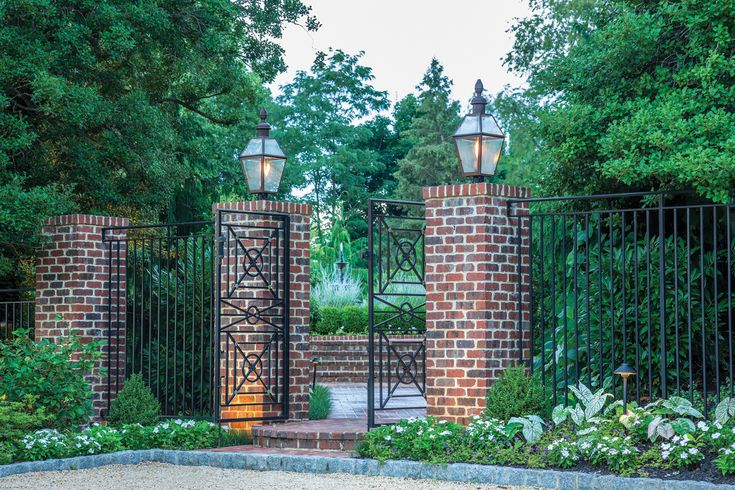 Brick Pillars Adorned With Wrought Iron Fencing Create A